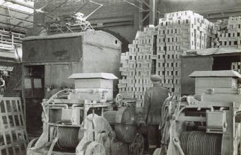 Interior of shed with stacks of bricks workman